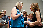 Republican presidential candidate Rep. Michele Bachmann, right, is embraced nine-year-old BrookLynn Anderson while talking to her mother, Candy Anderson after services at Living Word Outreach Ministries in Spencer, Iowa, July 31, 2011 while campaigning througout the state in advance of the Straw Poll.