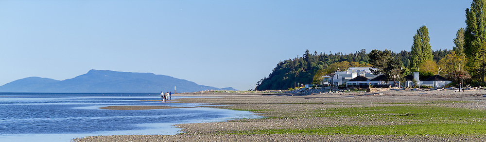 A Family watches the tide come into Centennial Beach at Boundary Bay Regional Park in Tsawwasen, British Columbia, Canada.  I watched them keep backing up to avoid it, only realize eventually that I was now standing in a few inches of water myself.