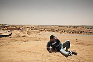 Observing a long and empty stretch of road in the desert, a  Libyan rebel on the watch at a frontline roadblock made of shipping containers and sand berms in Abdel-Rauf,  25 km south of Misrata. 04 June 2011.