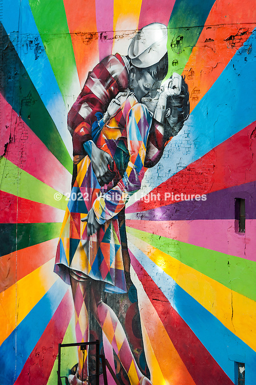 Mural painted on a brick wall depicting the classic photo of a sailor kissing a nurse in Times Square, New York City, on VJ day in 1945, with a colorful, modern twist.