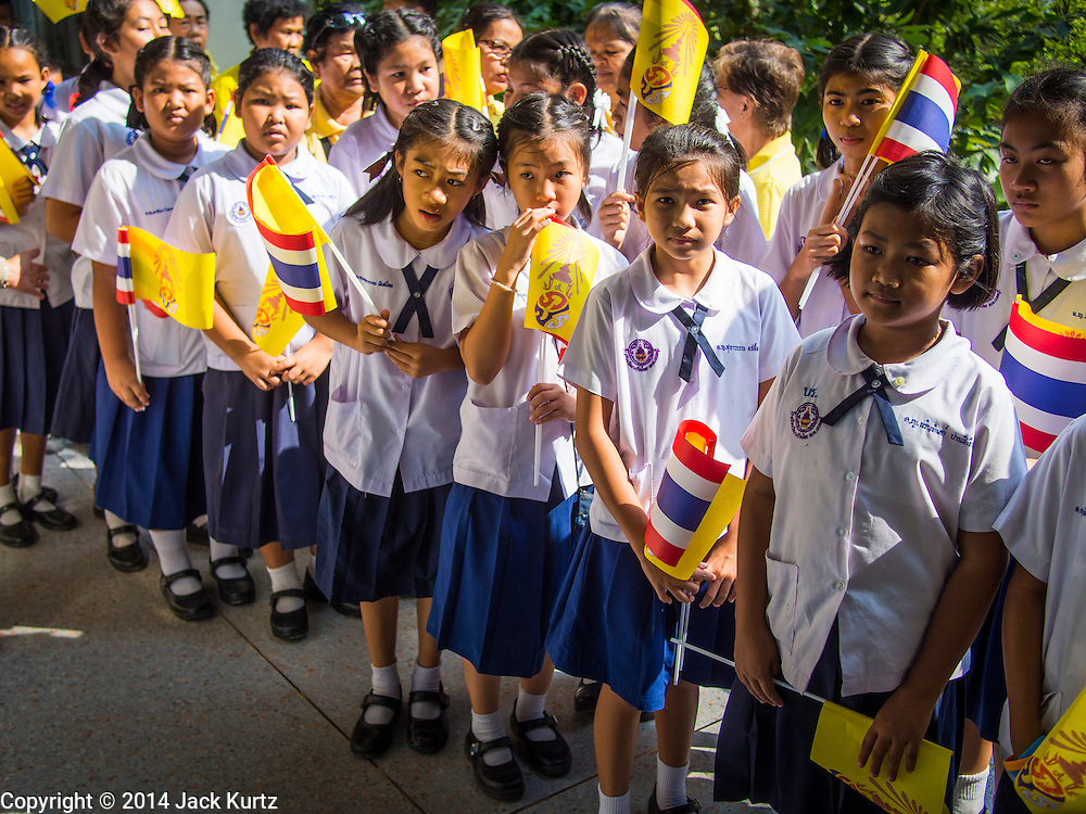 28 NOVEMBER 2014 - BANGKOK, THAILAND: School children with Thai flags and the yellow flag of the Thai monarchy line up to offer birthday wishes for Bhumibol Adulyadej, the King of Thailand. The King was born on December 5, 1927, in Cambridge, Massachusetts. The family was in the United States because his father, Prince Mahidol, was studying Public Health at Harvard University. He has reigned since 1946 and is the world's currently reigning longest serving monarch and the longest serving monarch in Thai history. Bhumibol, who is in poor health, is revered by the Thai people. His birthday is a national holiday and is also celebrated as Father's Day. He is currently hospitalized in Siriraj Hospital, recovering from a series of health setbacks. Thousands of people come to the hospital every day to sign get well cards for the King.       PHOTO BY JACK KURTZ