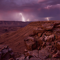 Africa, Namibia, Fish River Canyon National Park, Lightning strikes from storm clouds above walls of Fish River Canyon at dusk