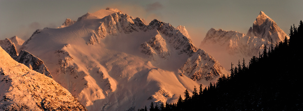 Unnamed mountain peaks near Sinclair Mountain in the Kakuhan Range bask in light from the setting sun in this sunset view seen from the Portage Cove harbor in Haines, Alaska. SPECIAL NOTE: DIGITAL COMPOSITE PANORAMA (multiple overlapping images stitched together)