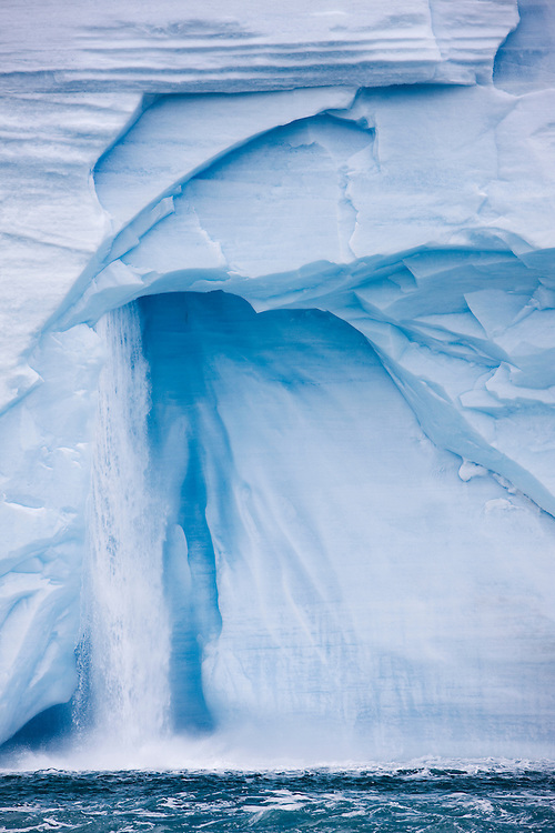 Norway, Svalbard, Nordaustlandet, Waterfall pours from ice face of Brasvellbreen Icefield on summer morning