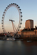 The old County Hall building and London Eye on the South Bank, at sunset, as seen from Westminster Bridge