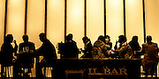 Japan. Silhouette of bar patrons in front of a screen of large backlit wall panels.