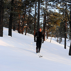 A man floats down a  hill in recently covered with a fresh coat of snow while backcountry skiing in the Zuni Mountains of New Mexico.