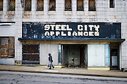 A woman walks past the old Steel City Appliances store on one of the main streets in Clairton, Pennsylvania on April 26, 2016. <br /> <br /> About three-quarters of its main street is boarded up including the laundry, the grocery store, three out of five banks, the three cinemas, and most cafes and shops.<br /> <br /> When the Clairton Coke Works employed 5,000 workers and ran three shifts, Clairton had three movie theaters and four car dealerships. Now the plant employs 1,300 workers and residents must drive five miles out of town to buy food since there is no longer a grocery store in town.