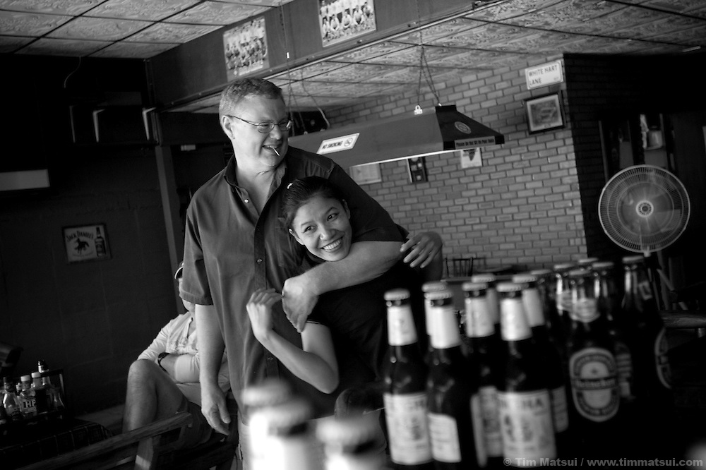 Eric, a mid-fifties Canadian expatriate and his mid-thirties Thai girlfriend Noi at the bar she manages in Chiang Mai, Thailand. Eric came to Thailand to escape depression and post traumatic stress from multiple accidents as a commercial truck driver, and found he can live well in the relatively inexpensive Thailand, not work, support Noi, and has bought land with the intention of building a home for himself and her family if they wish to move from their farm in Chiang Rai. Eric is quick to state he was never a sex tourist and while he met Noi at the bar she manages, it was a more innocent and drawn out affair more closely aligned with western dating practices than those of the Thai sex trade. Eric states that he is open with Noi about his finances and that he respects her wish to continue managing the bar and maintain her financial independence. As for Noi, she says she has never consider sex work, even though she could easily make twice her monthly salary of 6000 Baht (approx. $187). She has a low tolerance for flakiness in the 'bar girls' she manages and chooses to work the day shift so she can avoid being hit on by the many caucasian tourists looking for a 'date.'