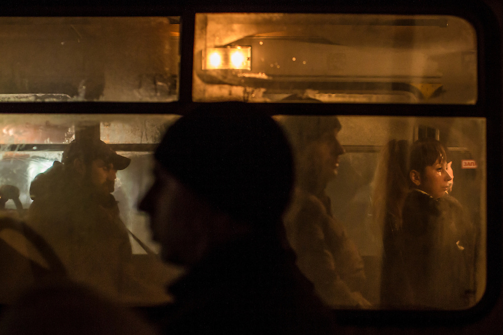DONETSK, UKRAINE - FEBRUARY 2, 2015: Passengers on a bus are seen through the window in Donetsk, Ukraine. With a rebel offensive against Ukrainian forces underway, the sound of artillery routinely echoes through the city while scores of civilians have been killed by shelling. CREDIT: Brendan Hoffman for The New York Times