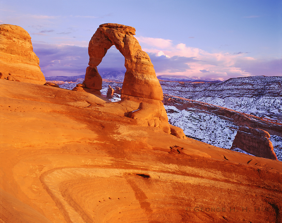 0301-1078LVT ~ Copyright: George H. H. Huey ~ Delicate Arch and La Sai Mountains at sunset with snow.  Arches National Park, Utah.