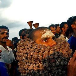 """A Hindu pilgrim worshipping Lord Shiva and the God of the Sea joins hundreds of fishing families from New beach in Nagapattinum district in Tamil Nadu, India as they take part in the unique ritual of reliving the day when Athi Baktha Nayanar found a gold fish in the ocean, offered it to his God and received """"moksha"""", September 2,2005. Villagers worship this God who is know to be the God of the Sea and the 49th nayanmar. The yearly ritual symbolizes an unwavering  pious man who always offered his daily catch to his God first, even when people in his village were starving. The ritual had been stopped for 25 years and many fishermen believed this is why the tsunami ravaged the coast of India.  (Ami Vitale)"""