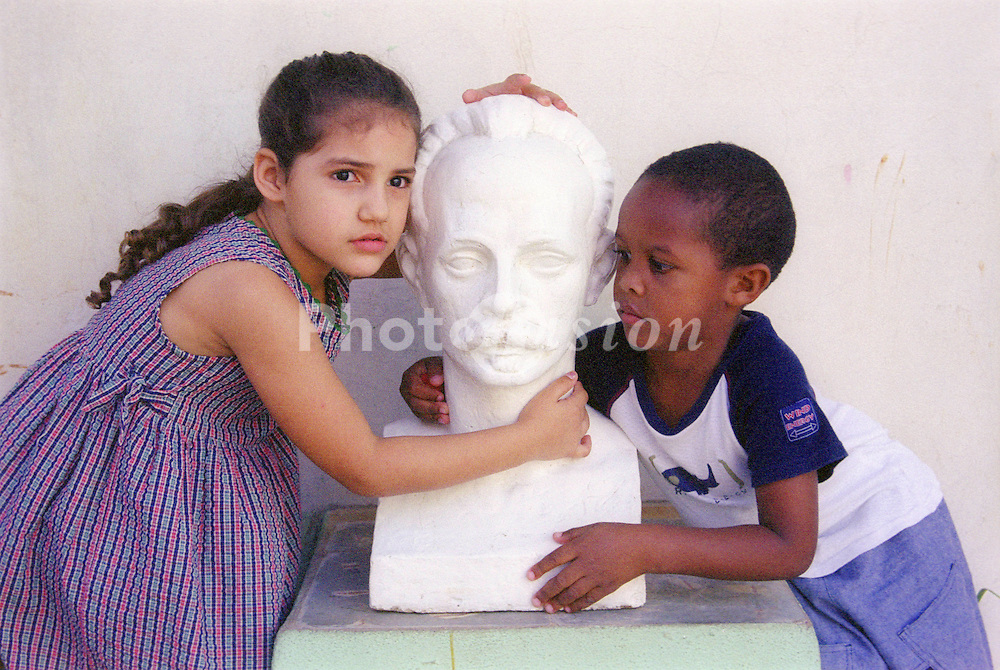 Cuban boy and girl with a bust of the famous statesman and poet; Jose Julian Marti,