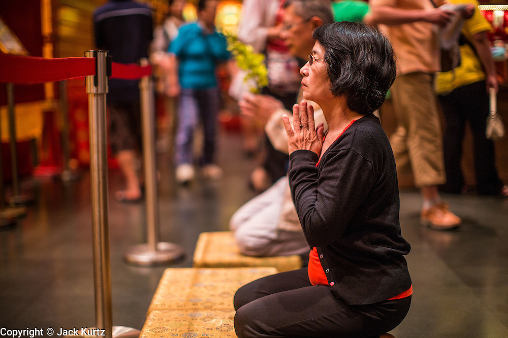 """16 DECEMBER 2012 - SINGAPORE, SINGAPORE:  A woman prays at the Buddha Tooth Relic Temple and Museum in the Chinatown section of Singapore. The temple houses a sacred Buddha tooth relic. It is a """"Mahayana"""" Buddhist temple, the larger of the two Buddhist sects. Mahayana Buddhism is practiced in India, China, Vietnam (northern), Japan, Tibet, Mongolia, Korea and in Chinese immigrant communities around the world.      PHOTO BY JACK KURTZ"""