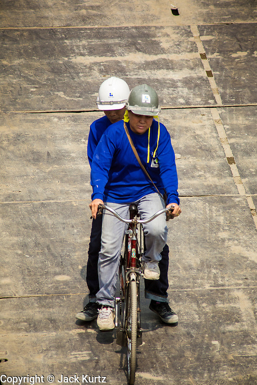 22 FEBRUARY 2013 - BANGKOK, THAILAND: Two workers ride a bicycle  at the Bhiraj Tower construction site. The Bhiraj Tower is new mixed use residential/office/retail complex under construction on Sukhmvit Road at Soi 33, across the street from the Emporium, a high end retail center. The Bhiraj should be finished in 2014 and will be 45 stories tall.       PHOTO BY JACK KURTZ