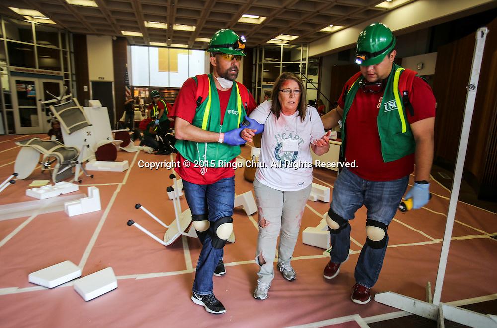 当地时间10月15日,搜救队把一名模拟地震受伤的&ldquo;伤者&rdquo;从现场救出。当天,在美国加利福尼亚州洛杉矶举行了第八届年度全球最大规模地震演习&ldquo;大摇晃&rdquo; (Great ShakeOut). 主办机构表示,加州有1,004万人签署参与,在全球其他地震区也有超过2000万人参与。(新华社发 赵汉荣摄)<br /> Members of Search And Rescue team rescue a mock victim during California's annual full-scale earthquake drill to prepare for a potential magnitude-6.7 earthquake in Los Angeles, California, Thursday, October. 15, 2015. About 10.4 million Californians and 21.5 million people worldwide who took part in safety drills and aftermath and recovery exercises in observance of the eighth annual Great ShakeOut.  (Xinhua/Zhao Hanrong)(Photo by Ringo Chiu/PHOTOFORMULA.com)
