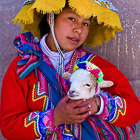 """CUSCO , PERU - MAY 27 : Unidentified Peruvian girl in traditional colorful clothes holding a lamb in here arms in the """" Unesco world heritage"""" city """"Cusco"""" on May 27 2011"""