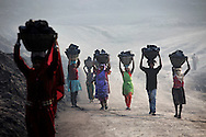 Villagers carry illegally scavenged coal from an open-cast coal mine in Dhanbad, Jharkhand, India on Dec 6, 2014, trying to earn a few dollars a day. <br /> (Photo by Kuni Takahashi)