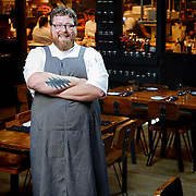 SHOT 8/15/13 4:22:00 PM - Justin Brunson, Owner and Executive Chef at Old Major, poses for a portrait in the main dining room at the restaurant in Denver, Co. The restaurant focuses on heritage-raised meats from Colorado farms, features an in-house butchery program and bills itself as contemporary farmhouse cuisine. (Photo by Marc Piscotty / © 2013)