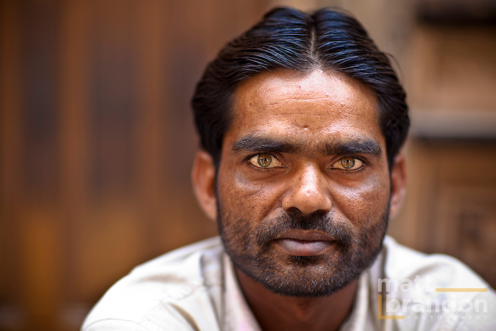 A man sits resting by the street side in Old Delhi.