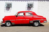 Shadows and old red car in San Juan y Martinez, Pinar del Rio, Cuba.