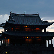 A temple near the reconstructed West Gate of the city gives off a warm inviting glow as the sun sets to the west.