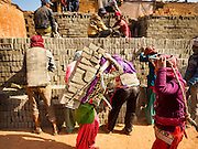 03 MARCH 2017 - BAGMATI, NEPAL: Workers stack wet, unbaked, bricks in a kiln at a brick factory in Bagmati, near Bhaktapur. There are almost 50 brick factories in the valley near Bagmati. The brick makers are very busy making bricks for the reconstruction of Kathmandu, Bhaktapur and other cities in the Kathmandu valley that were badly damaged by the 2015 Nepal Earthquake. The brick factories have been in the Bagmati area for centuries because the local clay is a popular raw material for the bricks. Most of the workers in the brick factories are migrant workers from southern Nepal.       PHOTO BY JACK KURTZ