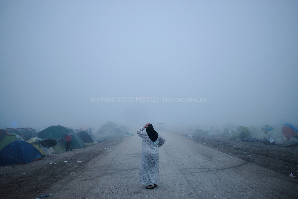 A veiled woman walks during the misty dawn at Idomeni refugee camp, on the Greek border with Macedonia.