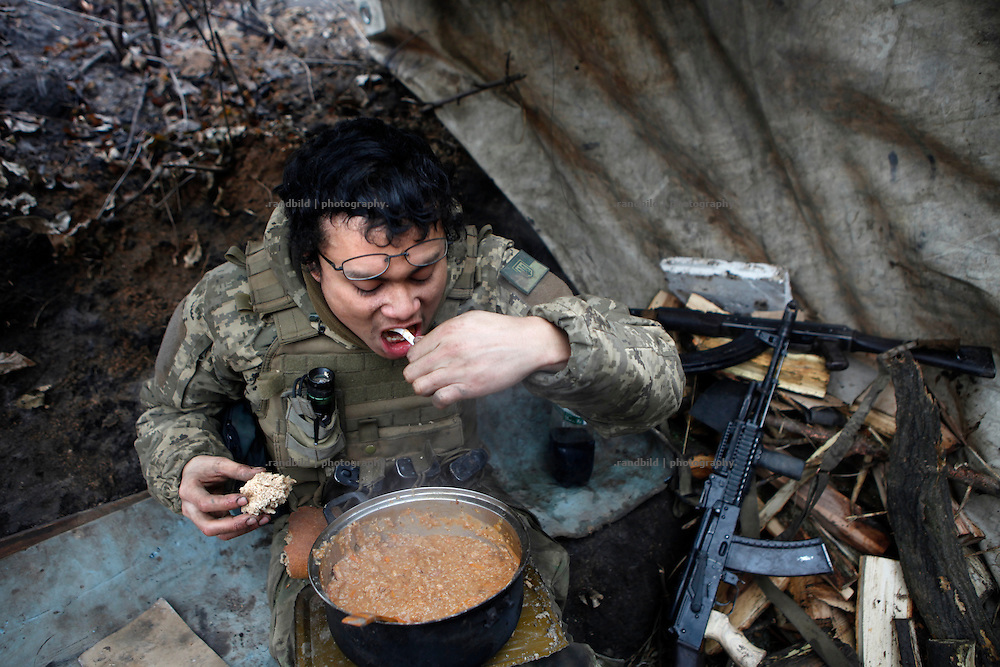Back in the trench from an exhausting re-supply mission under fire Charlie eats soup straight out of the pot.<br />