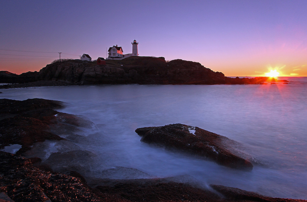 Maine Cape Neddick Nubble Lighthouse fine art photography is available as museum quality photography prints, canvas prints, acrylic prints or metal prints. Prints may be framed and matted to the individual liking and room decor needs:<br /> <br /> http://juergen-roth.artistwebsites.com/featured/maine-cape-neddick-nubble-lighthouse-juergen-roth.html<br /> <br /> Upon arrival at Sohier Park on Cape Neddick I explored various composition of Nubble Light but settled on this final composition because of the attractive foreground and the expected stunning sunrise. A neutral density filter enabled longer exposure times while a split neutral density filter managed the high contrast between the dark foreground and bright sky.<br /> <br /> The Nubble Lighthouse, near the town of York and York Beach, was built in 1879 because of many boating accidents in the Cape Neddick area. Nubble Light is also known as The Nubble and the Cape Neddick Lighthouse. The Nubble Lighthouse is a two layer brick lighthouse with a cast iron outer shell to the lighthouse with a red blinking beacon to warn ship captains. There is a walkway between the Nubble Light and the house that was constructed for the lighthouse keeper. It protected the keeper from bad weather when the lighthouse was needed most. Although originally equipped with a bell on the lighthouse that was utilized during bad weather, it now has a fog horn since 1961. The lighthouse is now fully automated. Therefore there is no lighthouse keeper and the US Coast Guard maintains the Nubble Light. The island is owned and maintained by the town of York Maine. The Nubble Lighthouse is best viewed and photographed at Sohier Park on Cape Neddick.<br /> <br /> Good light and happy photo making!<br /> <br /> My best,<br /> <br /> Juergen<br /> www.RothGalleries.com<br /> www.ExploringTheLight.com<br /> http://whereintheworldisjuergen.blogspot.com<br /> @NatureFineArt<br /> https://www.facebook.com/naturefineart