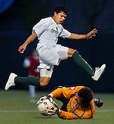 The Timbers' Byron Alvarez (15) jumps over Edmonton's goalie Nicola Stankov (1) who pulls in a shot on goal. The Portland Timbers beat the Edmonton Aviators 6-0..