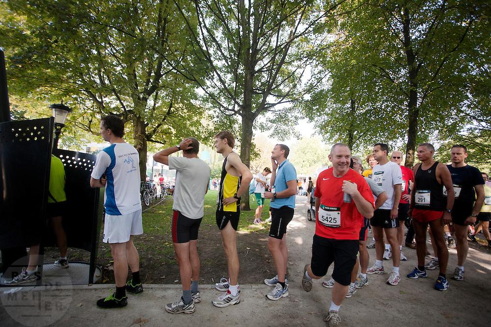 Mannelijke deelnemers aan de Singelloop staan voor de start geduldig in een rij voor het urinoir. In Utrecht is de 61e Singelloop gehouden, die sinds vorig jaar in de boeken staat als het snelste 10 km parcours.<br /> <br /> Men are lining up at a urinal at the start of the 10km running race.