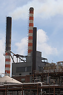 Two large smoke stacks stand tall over a factory in Pekin, IL.