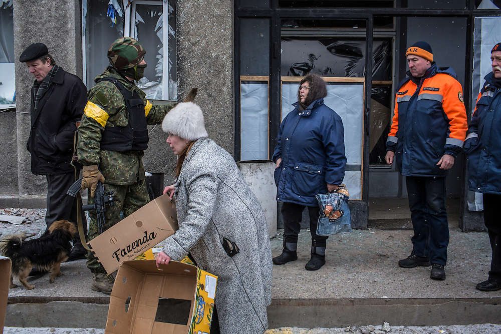 DEBALTSEVE, UKRAINE - FEBRUARY 7, 2015: Loafs of bread are handed out to people gathered outside a municipal building in Debaltseve, Ukraine. The Ukrainian-controlled town, surrounded on three sides by rebel forces, has been undergoing heavy shelling for more than a week, but a brief ceasefire allowed many residents to evacuate and others to simply venture out from their homes. CREDIT: Brendan Hoffman for The New York Times