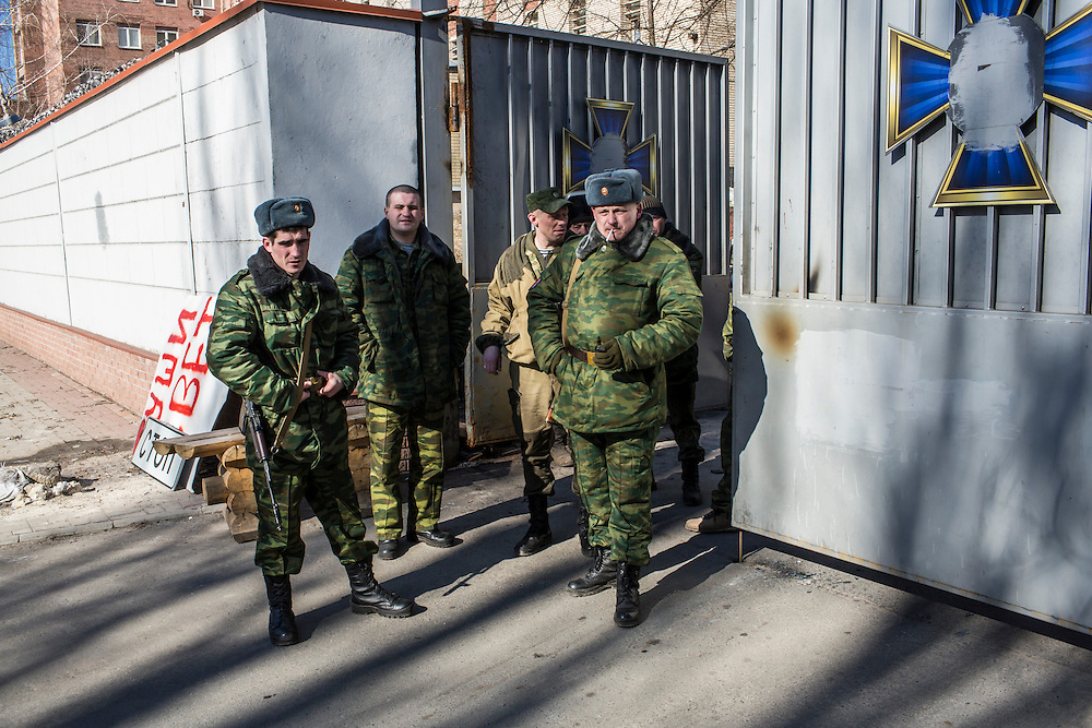 DONETSK, UKRAINE - FEBRUARY 21: Pro-Russian rebels stand outside the gate to one of their bases on February 21, 2015 in Donetsk, Ukraine. A ceasefire agreement between rebels and Ukrainian forces is at risk of falling apart after fierce fighting forced the Ukrainians to withdraw from the strategic town of Debaltseve. (Photo by Brendan Hoffman/Getty Images) *** Local Caption ***