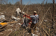 Rainsville, Alabama: Shane Spillmen, from Fort Payne, helps a neighbor sift through a valley of debris, and finds an American flag, in this rural northeastern Alabama town. At least 32 people are confirmed dead in Rainsville and surrounding Dekalb County. (PHOTO: MIGUEL JUAREZ LUGO)