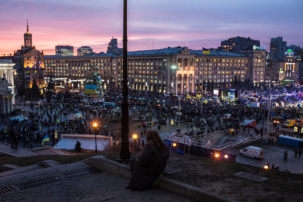 KIEV, UKRAINE - DECEMBER 4: A woman watches anti-government protesters rally in Independence Square at sunset on December 4, 2013 in Kiev, Ukraine. Thousands of people have been protesting against the government since a decision by Ukrainian president Viktor Yanukovych to suspend a trade and partnership agreement with the European Union in favor of incentives from Russia. (Photo by Brendan Hoffman/Getty Images) *** Local Caption ***