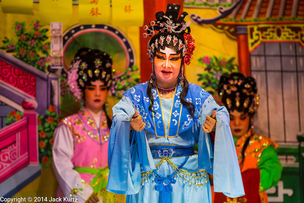 "19 AUGUST 2014 - BANGKOK, THAILAND:  Members of the Lehigh Leng Kaitoung Opera troupe perform at a Chaomae Thapthim Shrine, a small Chinese shrine in a working class neighborhood of Bangkok. The performance was for Ghost Month. Chinese opera was once very popular in Thailand, where it is called ""Ngiew."" It is usually performed in the Teochew language. Millions of Chinese emigrated to Thailand (then Siam) in the 18th and 19th centuries and brought their culture with them. Recently the popularity of ngiew has faded as people turn to performances of opera on DVD or movies. There are still as many 30 Chinese opera troupes left in Bangkok and its environs. They are especially busy during Chinese New Year and Chinese holiday when they travel from Chinese temple to Chinese temple performing on stages they put up in streets near the temple, sometimes sleeping on hammocks they sling under their stage. Most of the Chinese operas from Bangkok travel to Malaysia for Ghost Month, leaving just a few to perform in Bangkok.        PHOTO BY JACK KURTZ"