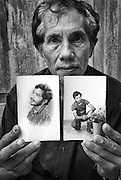Yeronimo Yoaquim Galucho, 42 years old and his neighbor Malicoli, 65 years old, killed by rampaging Militia Dili East Timor in 1999. Here Galucho's brother holds two photos of Yeronimo as a young man.