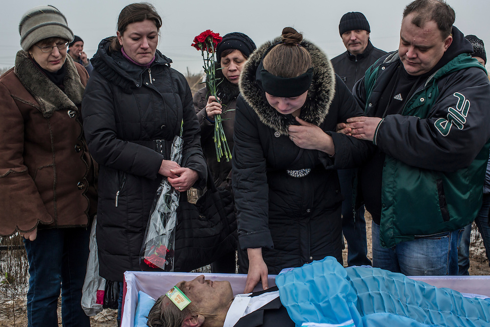 DONETSK, UKRAINE - JANUARY 30, 2015: Lyudmila Bogdan, center, grieves at the funeral at Yuzhnaya Cemetery of her father Anatoliy Bogdan, 54, who was killed by shelling on January 27 in Donetsk, Ukraine. At least seven people were killed in two shelling incidents in Donetsk today, the deadliest day for civilians in more than a week, as peace talks in the Belarussian capital of Minsk were postponed. CREDIT: Brendan Hoffman for The New York Times