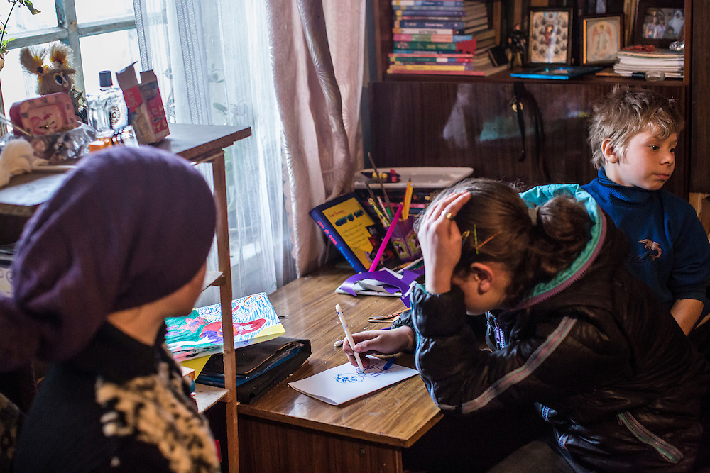Diana, age 11, Elena, age 13, and Nikolai, age 9, listen as a military chaplain tries to convince their families to allow the children to move away from the dangers of life on the front line on Saturday, February 13, 2016 in Zaitseve, Ukraine. The town itself is half controlled by Ukrainian forces and half by pro-Russian rebels, leading to regular fighting.