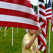 """Connor Cuthbert, 9, unfurls a flag while helping set up """"Field of Hopes and Dreams"""" Memorial Day flag installation at Hoopes Park.  A dedication was sold for each of the 1,200 flags to raise funds for St. Joseph's School."""