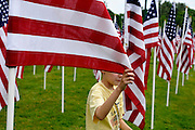 "Connor Cuthbert, 9, unfurls a flag while helping set up ""Field of Hopes and Dreams"" Memorial Day flag installation at Hoopes Park.  A dedication was sold for each of the 1,200 flags to raise funds for St. Joseph's School."