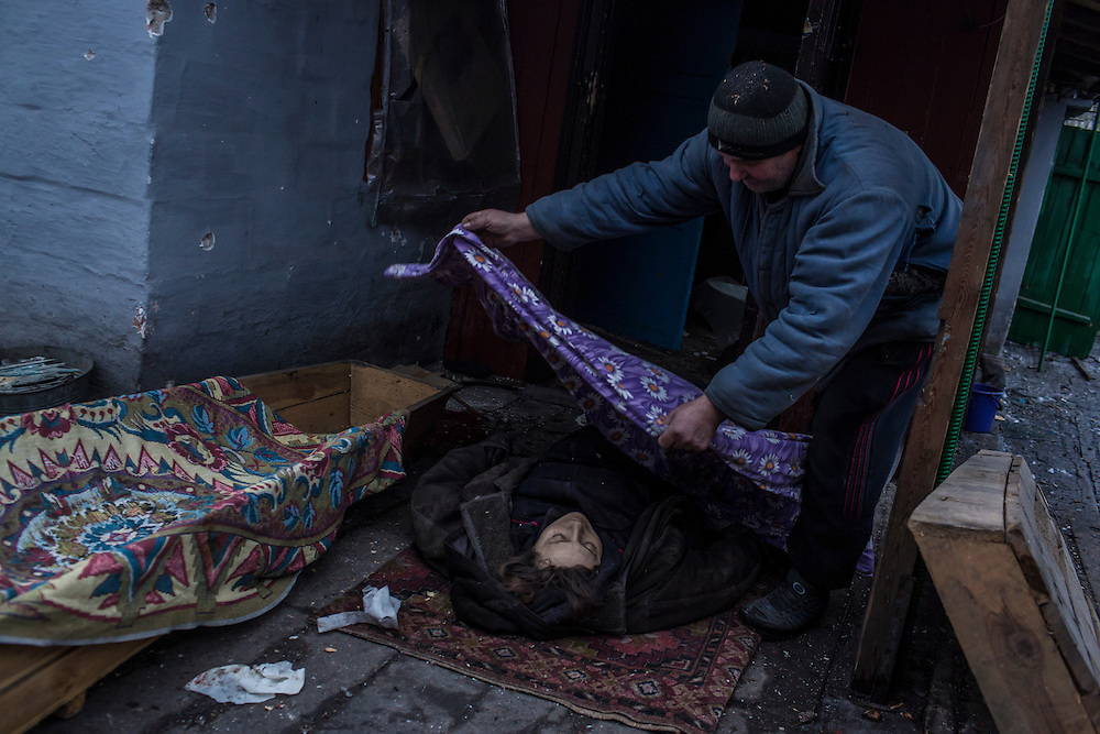 DONETSK, UKRAINE - JANUARY 28, 2015: A man covers the body of a woman killed by shelling outside her house earlier in the day in the Petrovskyi district of Donetsk, Ukraine. The area, in the city's southwest, is close to heavy front-line fighting in Marinka. CREDIT: Brendan Hoffman for The New York Times