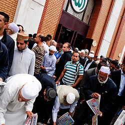 London, UK - 20 July 2012: Muslim faithful  picks up newspapers outside of the East London Mosque during the first day of Ramadan.