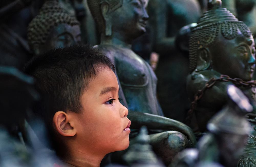 A boy amongst Buddha statues at a market in Bangkok, Thailand.