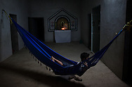 "A young boy in rests in a hammock in San Dionisio...The Isthmus of Tehuantapec, long a center for indigenous land ownership, is now embroiled in a land dispute over wind farm land...Called ""Mexico's little waist,"" the Isthmus is a wind tunnel that links the Gulf of Mexico to the Pacific through mountain passes at the narrowest part of Mexico. The geographical funnel makes it one of the windiest places in North America and for a decade wind energy companies have been jostling to acquire land to power the likes of Coca-Cola and Wal Mart."