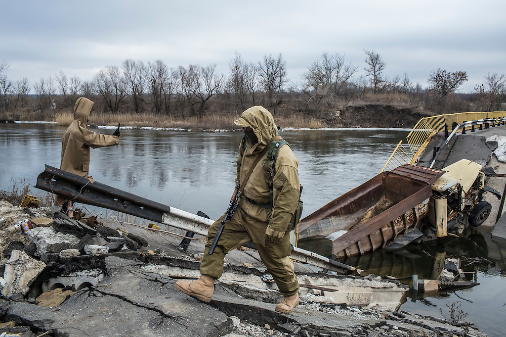Ukrainian soldiers guard a destroyed bridge over the Siverskyi Donets River, which separates Ukrainian territory from that controlled by pro-Russian rebels, on Wednesday, February 10, 2016 in Trokhizbenka, Ukraine.