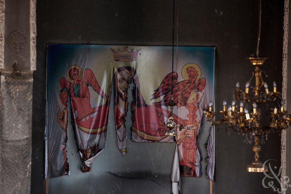 A damaged poster of Jesus remains above the altar inside the burned and looted Virgin Mary Church August 20, 2013 after a recent attack by Muslims in the village of Nazla, near el Fayoum, around a 100 kilometers South of Cairo, Egypt.  Coptic Christian villagers report 2 churches and a monastery in the area came under attack by their Muslim neighbors on the same day as Egyptian security forces were moving to forcibly disperse the sit-in camp of the supporters of deposed president Mohamed Morsi.