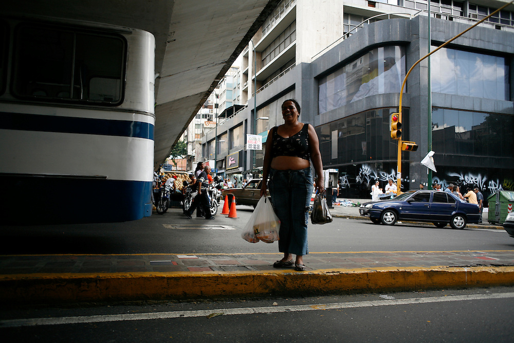 A woman carries her groceries in downtown Caracas.